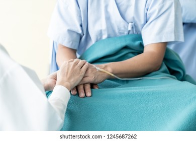 Hand of female doctor reassuring on her senior patient - selective focus point