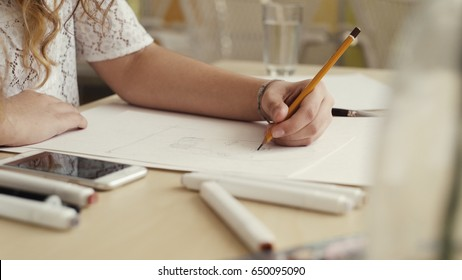 Hand of female drawing at paper in her studio. woman's hand draws a pencil. Designer clothes or tailor, animator, artist or illustrator.
