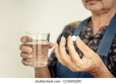 Hand of female elderly holding a white medicine
