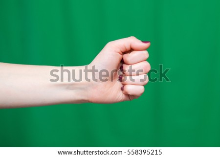 Hand female fist closeup on a green background