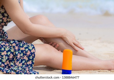 Hand of female holding sunscreen applying sunscreen on her hands from a bottle on the beach with the sea /Health concepts and skin care.