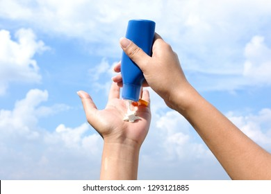 Hand of female holding sunscreen. Very sun light Sky background.Health concepts and skin care