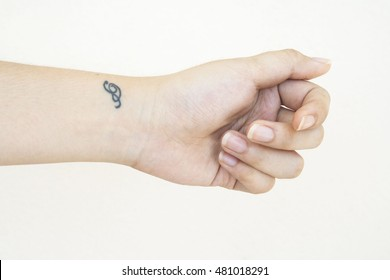 hand of female with little tattoo at wrist on background white