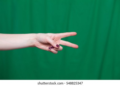 Hand female with two fingers, the world closeup on a green background