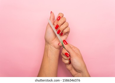 Hand filing nails with glass nail file on the pink background