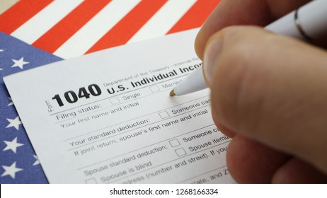 Hand filling american 1040 Individual Income Tax return form on table with US flag at home