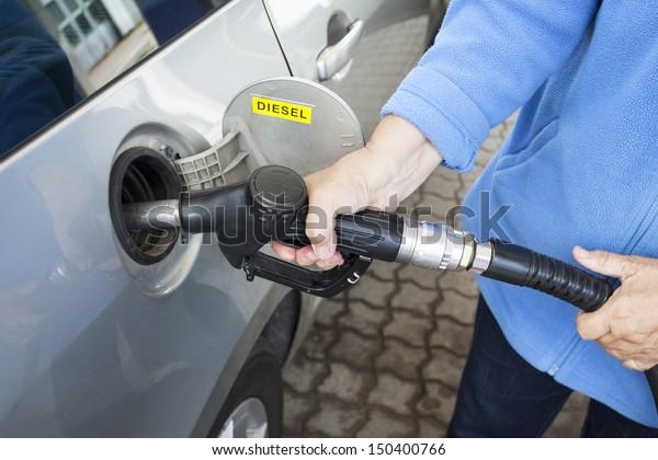 Une main qui remplit une voiture avec du diesel
