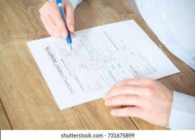 Hand filling the unemployment benefit application