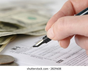 Hand filling W-9 income tax form with pen