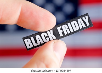 Hand with fingers holding a black friday sticker on the background of the American flag.