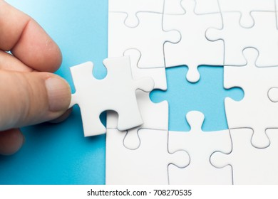 A hand fitting the last piece of puzzle in place, business concept for completing the final puzzle piece