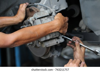 Hand fixing car's brake system in a garage