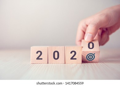 Hand flip over wood wooden cubes with New year 2020 and goal icon concept.