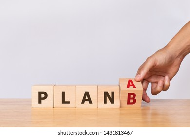 Hand flip wooden cube with the word PLAN A to PLAN B on white background. Business concept