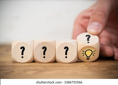 hand is flipping one of many cubes with questionmarks to find an idea symbol on wooden background