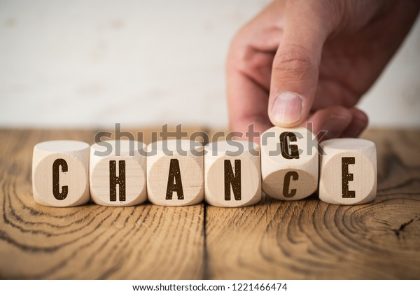 """hand flipping one of six cubes, turning the word """"change"""" to """"chance"""""""