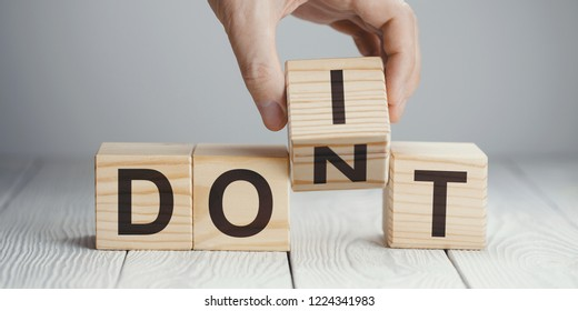 "Hand flipping one wooden cube to change the word ""Don't"" for ""Do it"" on neutral background"
