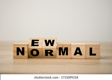 Hand flipping wooden block cubes for new normal wording. The world is changing to balance it into new normal include business , economy , environment and health.