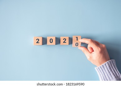 Hand flipping wooden blocks for change year 2020 to 2021 on blue paper background. New year and holiday concept.