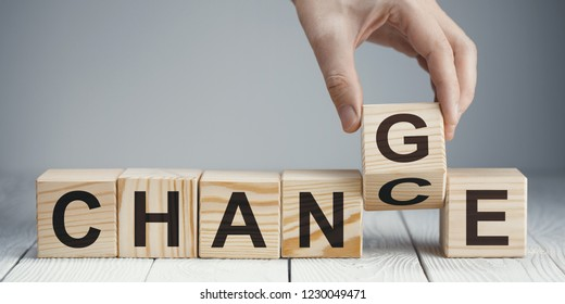 """Hand flipping a wooden cube to remove the word """"Chance"""" by """"Change"""" or vice versa on neutral background"""