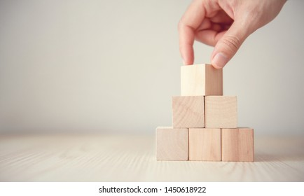 Hand flips blank wood cube block on top pyramid, for create icon symbol to success concept.