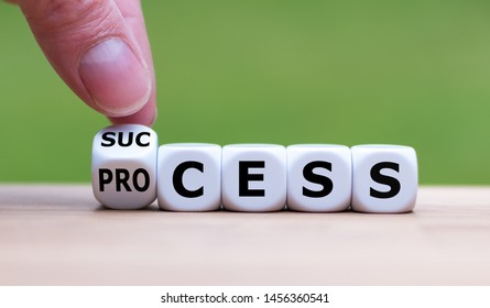 """Hand flips a dice and changes the word """"process"""" to """"success""""."""
