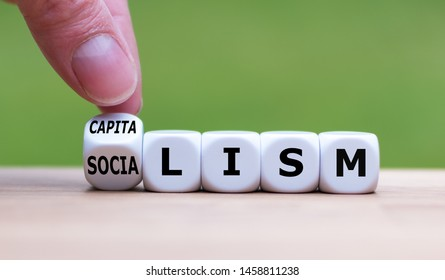 """Hand flips a dice and changes the word """"Socialism"""" to """"Capitalism"""", or vice versa."""