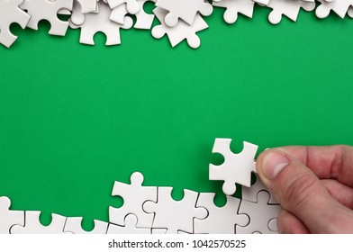 The hand folds a white jigsaw puzzle and a pile of uncombed puzzle pieces lies against the background of the green surface. Texture photo with space for text