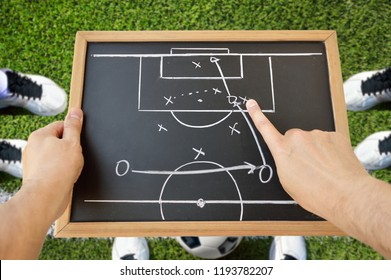 hand of a football coach drawing a tactics of soccer game with white chalk on blackboard at stadium background
