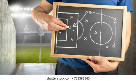 hand of a football coach drawing a tactics of soccer game with white chalk on blackboard at arena tunnel