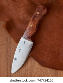 Hand forged high carbon steel knife with rough edges and forging marks with redwood burl handle photographed on leather and wood surface.