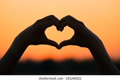 hand forming a heart shape with sunset silhouette
