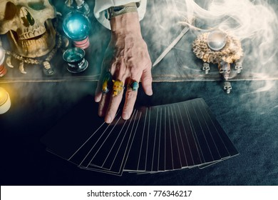 Hand of fortune teller and tarot card on the table under candlelight. Dark tone.