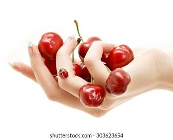 hand full of red cherries over white background