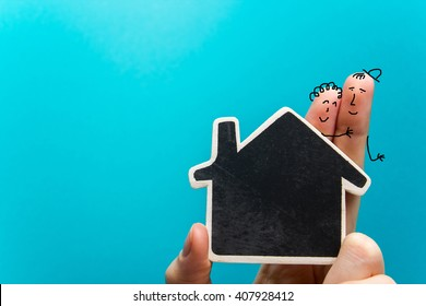 Hand with funny fingers holding white paper house figure on blue background. Real Estate Concept. Copy space top view.