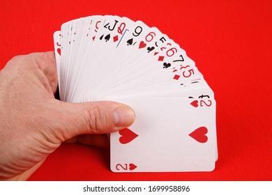 Main avec carte de jeu isolée sur fond rouge