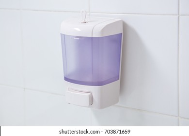 Hand gel soap box pump on white wall in toilet.