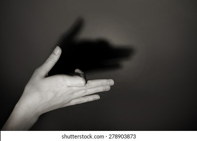 Hand gesture like dog face on gray background
