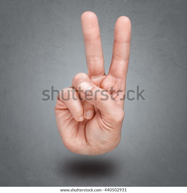 Hand gesture of victory and peace. Isolated over gray background.