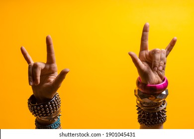 Hand gestures. Thumbs up, that's a cool gesture of the rocker. women's hand with lots of bracelets, youth fun style. bright yellow background