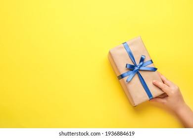 Hand with gift on color background