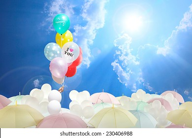 Hand girl clutching ropes balloon colorful wrote congratulations and print words I love you. rises above umbrellas light and white balloons. on the blue sky with sun rays shining through the clouds.