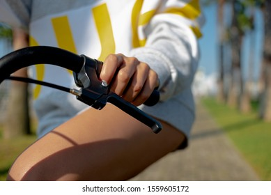 hand of a girl in a gray white hoodie with yellow letters on the handrail of a yellow Bicycle, close-up