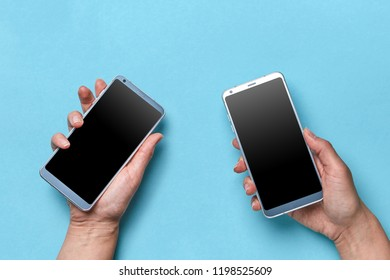The hand of the girl and the man hold modern mobile phones on a blue background with copy space for text. Flat lay