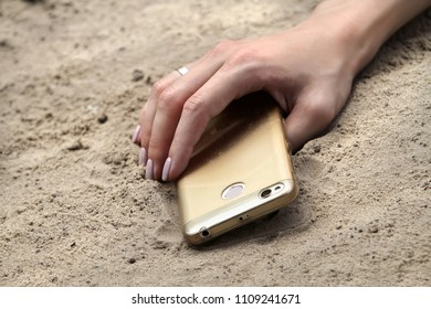 The hand of a girl with a mobile phone lies on the sand. Hand a girl with an engagement ring lies on a mobile phone on the beach.