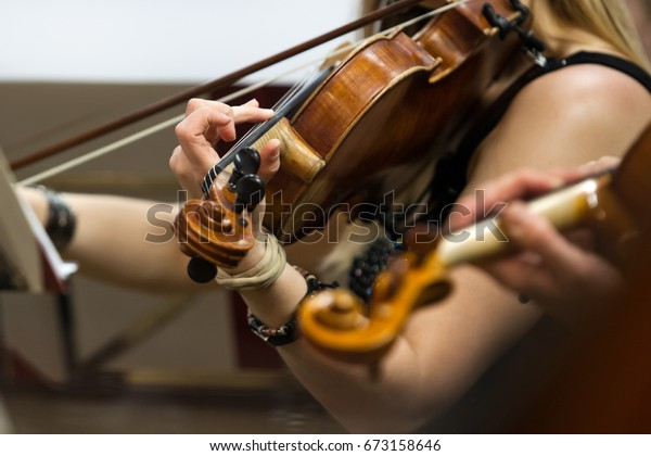The hand of a girl playing the violin in an orchestra