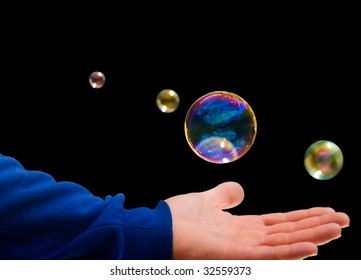 The Hand of a Girl plays with a Soap bubble