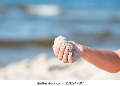 Hand of girl pouring sands. Summer. Holiday. Sea.