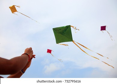 Hand of a girl raises a kite in a sky where some other kites are also flying