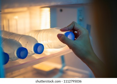 Hand of a girl taking out a water bottle or mineral water from refrigerator or a fridge on bed room or hotel. Drinking water is beneficial to health.